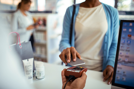 Shopper making digital payment in store with tap and pay through iPhone