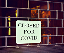"""Showcasing sign outside store stating: """"Closed for Covid"""""""